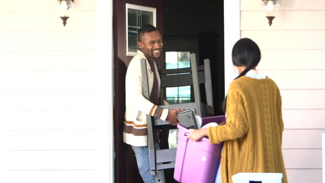 Young couple moving, carrying belongings in front door video