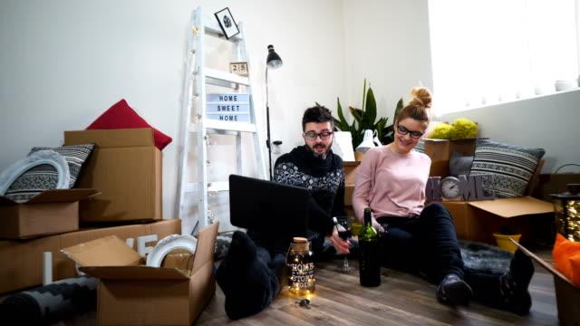 unga par moving i nya hem. sitter på golvet och avkopplande efter rengöring och uppackning. ser något på laptop. - wine box bildbanksvideor och videomaterial från bakom kulisserna