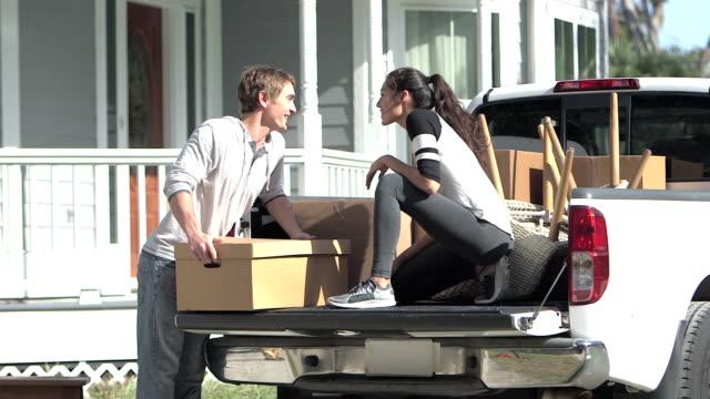 young couple moving, unloading boxes from pick-up truck - rozładowywać filmów i materiałów b-roll