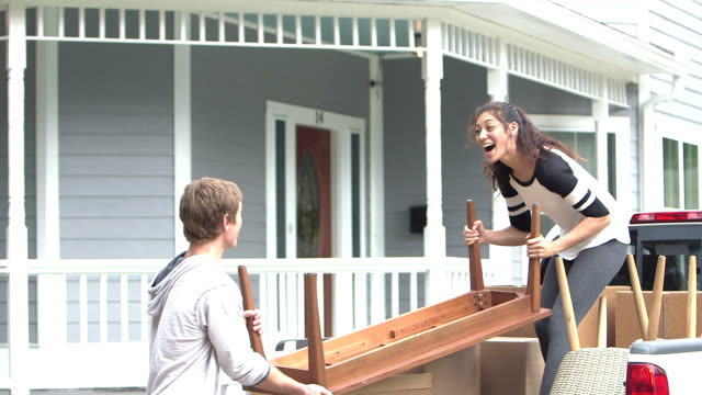 Young couple moving, unloading table from pick-up truck video