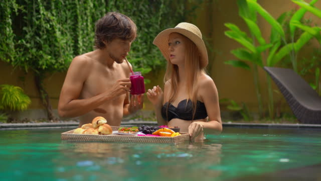 a young couple of honeymoon tourists have their own personal breakfast on a floating table in a private swimming pool. tropical beach lifestyle - дворец спорта стоковые видео и кадры b-roll