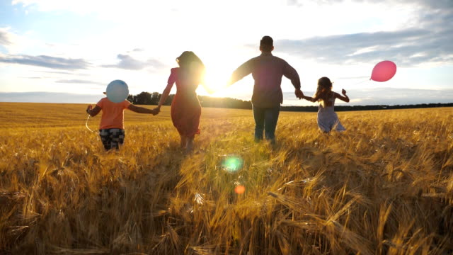 Young couple of parents with two children holding hands of each other and running through wheat field at sunset. Happy family jogging among barley meadow and enjoying nature together. Slow motion