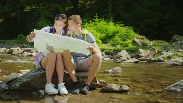 A young couple of tourists are studying together a map. They sit in a picturesque place near a mountain river. Copyspace composition video