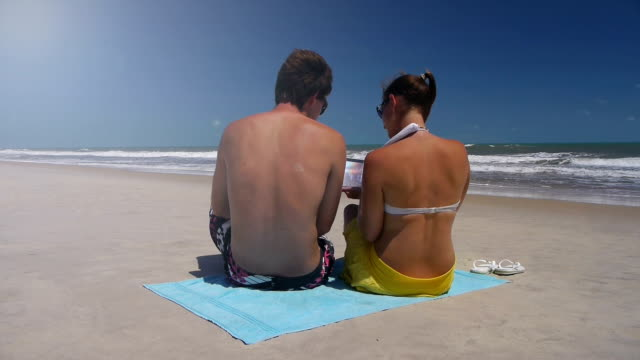 Young couple on a beach, using digital tablet video