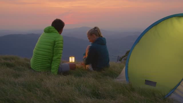 close up: junges paar auf einem campingausflug bei einem ruhigen abend in den alpen - freizeitaktivität im freien stock-videos und b-roll-filmmaterial