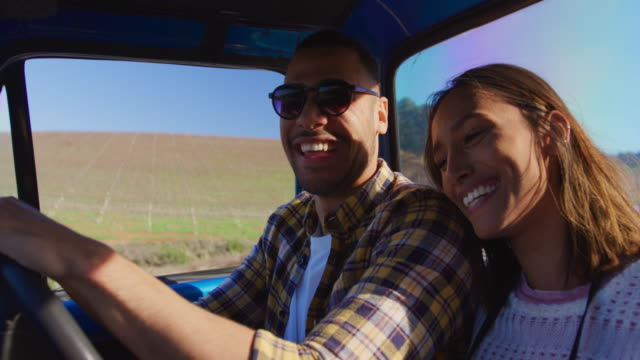 Young couple on a road trip in their pick-up truck Side view close up of a young mixed race couple sitting in their pick-up truck, smiling and embracing during a road trip leaning stock videos & royalty-free footage