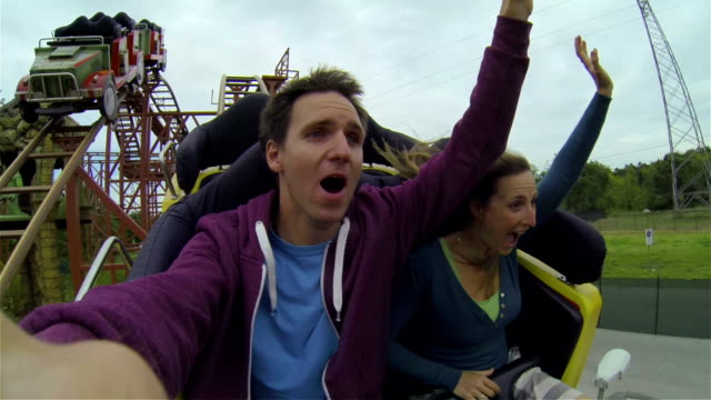 young couple on a rollercoaster - roller coaster stock videos & royalty-free footage
