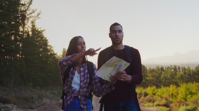 stockvideo's en b-roll-footage met jong stel op een trektocht op het platteland - roadmap