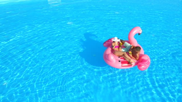 AERIAL Young couple on inflatable flamingo is annoyed by annoying bees and flies video
