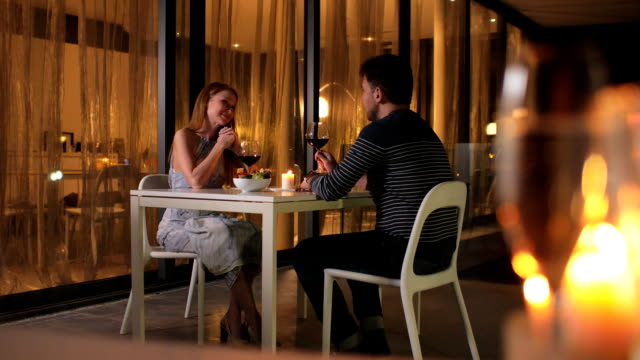 Young couple on the first date in the restaurant. The girl talks too much, the man suffers video