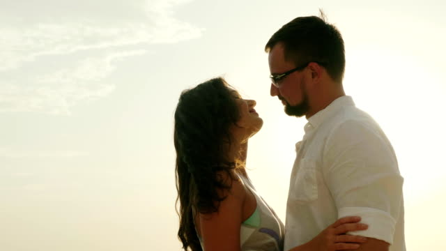 Young couple on vacation by the sea. Kiss on the background of the sky and the sun video