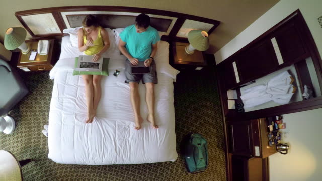 TOP DOWN: Young couple on vacation working on their laptops while sitting on bed
