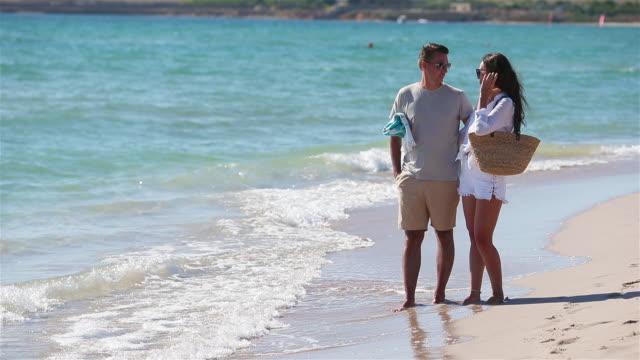 vídeos y material grabado en eventos de stock de pareja joven en la playa blanca durante las vacaciones de verano - espalda humana