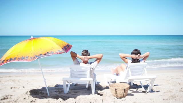 vídeos y material grabado en eventos de stock de pareja joven en la playa blanca durante las vacaciones de verano. - espalda humana