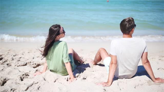 yaz tatilinde beyaz plajda genç çift - i̇nsan sırtı stok videoları ve detay görüntü çekimi
