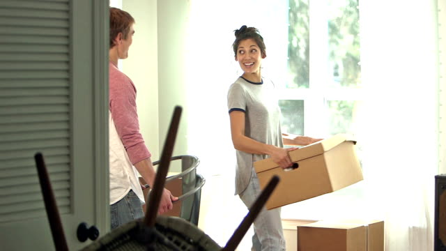Young couple packing up and moving out of house A young couple in their 20s moving. They are inside a house or apartment, picking up furniture and boxes. young couple stock videos & royalty-free footage