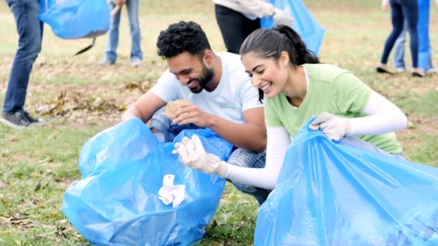Young couple participate in community cleanup day Young Indian man and young Hispanic woman smile and laugh with one another while picking up garbage in their community park. They are kneeling down picking up various pieces of garbage. Their neighbors are working in the background. sociology stock videos & royalty-free footage