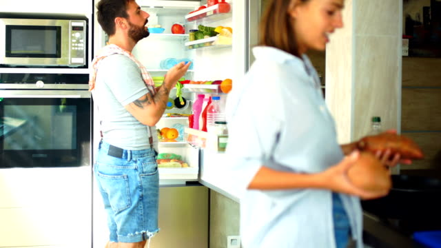Young couple picking up some fruits and veggies from the fridge.