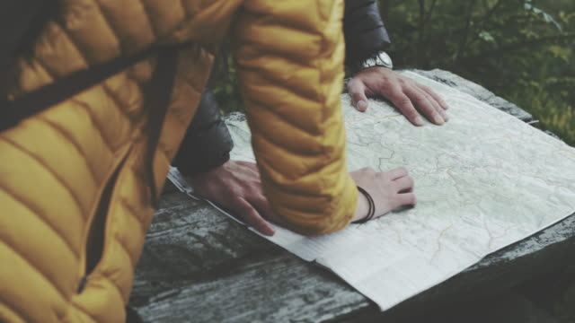 Young couple planning their trip with map. Close up video