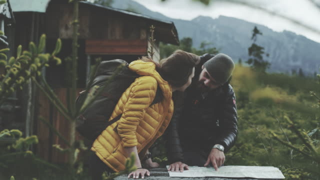young couple planning their trip with map - дикая местность стоковые видео и кадры b-roll