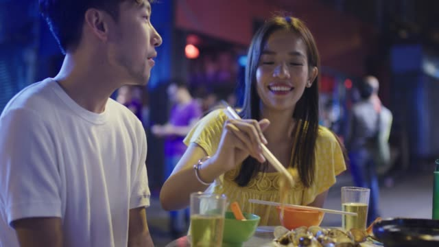 young couple playfully eating street food - date night stock videos & royalty-free footage