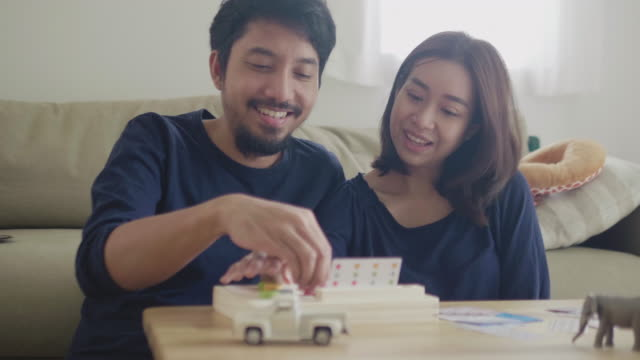 young couple playing board game - vivere semplicemente video stock e b–roll
