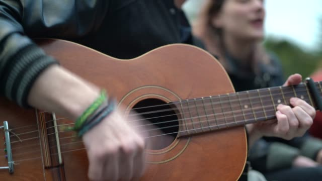 unga par spelar gitarr på city - akustisk gitarr bildbanksvideor och videomaterial från bakom kulisserna