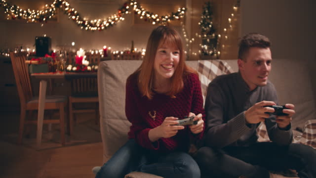 a young couple playing video games on christmas evening. - treedeo stock videos & royalty-free footage