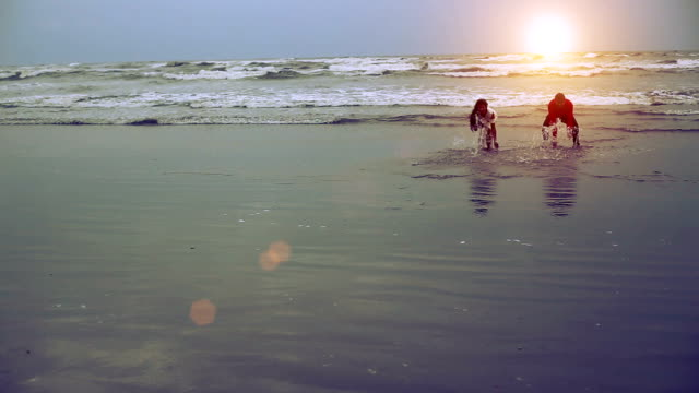 Young couple playing with sea water
