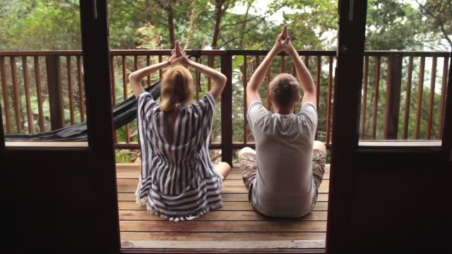 young couple practicing yoga on the terrace in the jungle - balcone video stock e b–roll