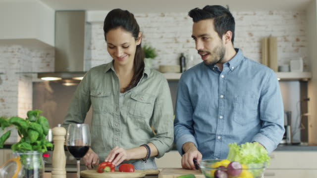 Young Couple Prepares Food on the Kitchen. They are Cutting Vegetables and Talking. Smiling to Each Other. video