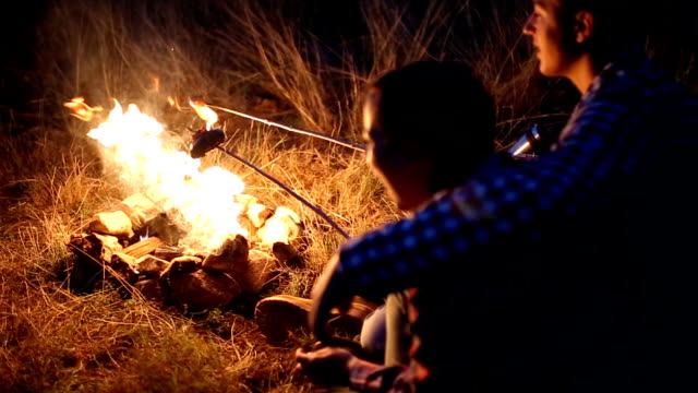 Young couple preparing meal on campfire video