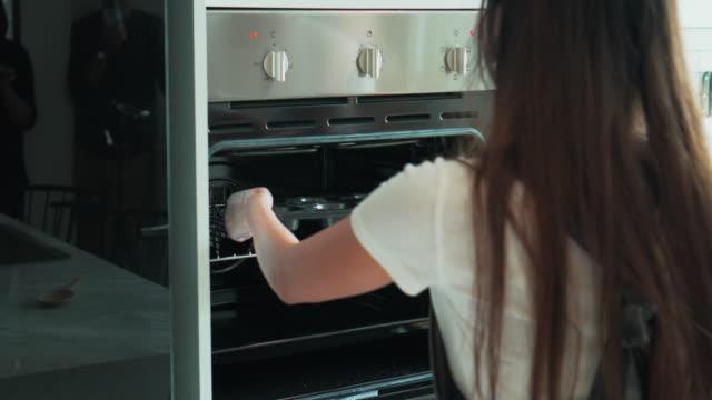 vidéos et rushes de jeune couple met le pain dans le four - four