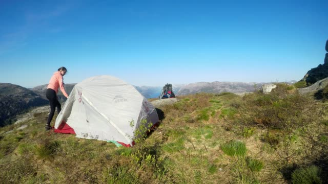 A young couple putting up the tent in the nearby of Preikestolen, Norway. Wild camping in the nature. Couple is having fun. Lysefjord in the back, going far inside the land. Freedom and adventure.