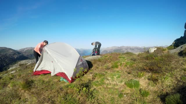 A young couple putting up the tent in the nearby of Preikestolen, Norway. Wild camping in the nature. Girl builds up the tent, boy brings more things. Lysefjord in the back, going far inside the land.