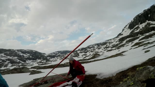 A young couple putting up the tent in the nearby of Trolltunga, Norway. Wild camping in the nature. Couple is having fun. They are surrounded by snow. Winter mountain climbing. Freedom and adventure.