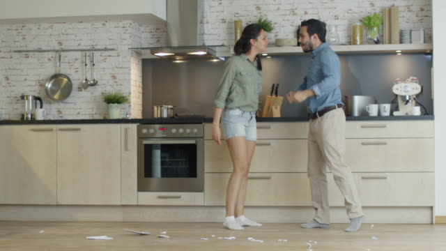 Young Couple Quarrels in the Kitchen. Girl Had Enough and She Breaks the Plate. Man Screams in Frustration and Angrily Gesticulates. Slow Motion. - vídeo
