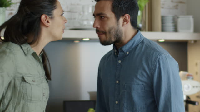 young couple quarrels in the kitchen. man and woman scream  in frustration and angrily gesticulate. slow motion. - conflittualità video stock e b–roll