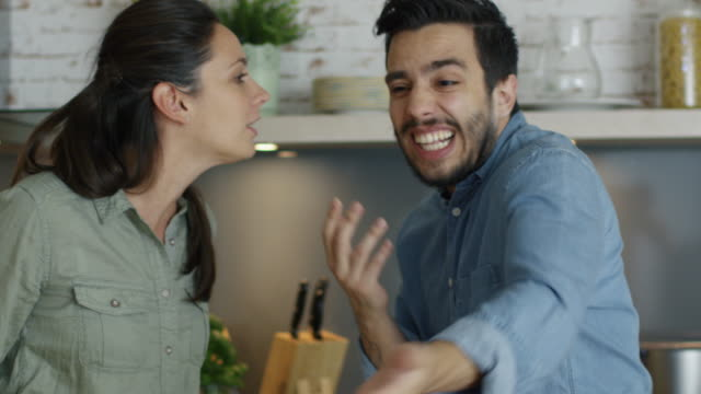 vídeos de stock e filmes b-roll de young couple quarrels in the kitchen. man and woman scream  in frustration and angrily gesticulate. - brigar