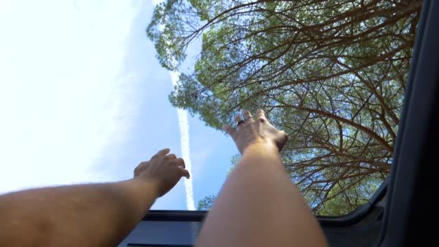 pov: young couple raising their arms through sunroof during summer road trip. - pojazd lądowy filmów i materiałów b-roll