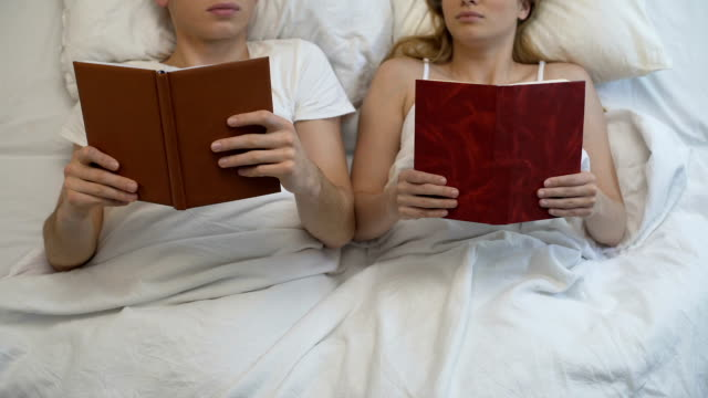 Young couple reading books in bed ignoring each other, intimate problem, rest video