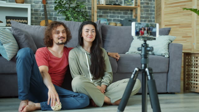 Young couple recording video for internet vlog in apartment using smartphone camera