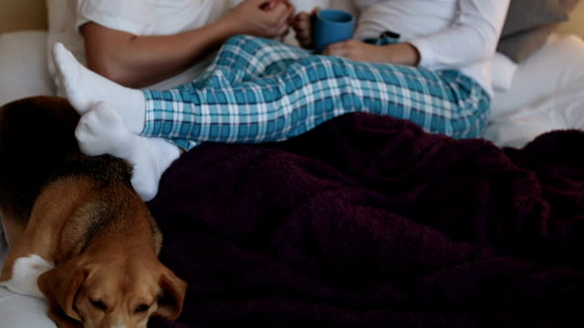 Young Couple Relaxing In Bed With Hot Drink video