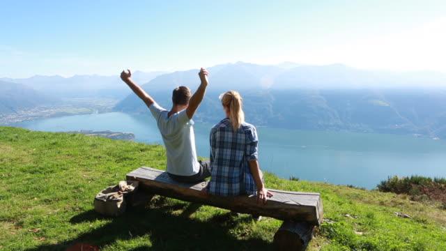 vídeos de stock e filmes b-roll de casal jovem relaxante na bancada, scenic vista - lago maggiore