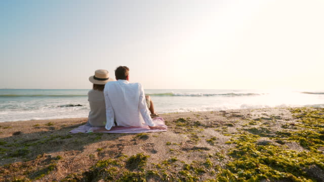 Young couple relaxing. Young couple sitting on the beach and enjoying the view. newlywed stock videos & royalty-free footage