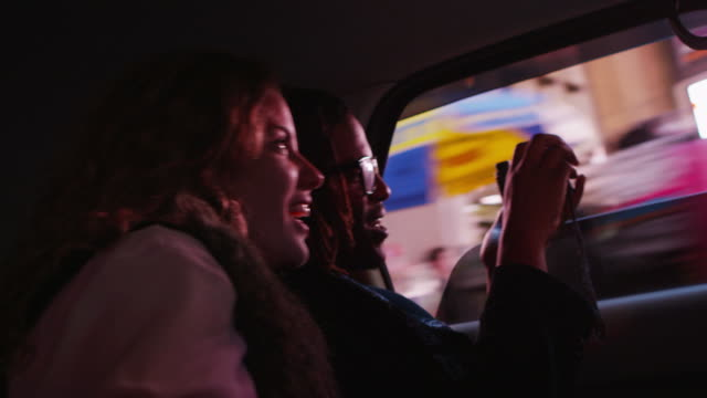 young couple riding in taxi cab, new york city - 景深 個影片檔及 b 捲影像