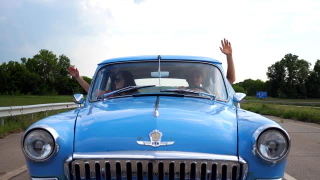 vidéos et rushes de jeune couple dans une voiture vintage et jouant avec le vent à voyage estival. homme et femme assise sur le siège avant de la vieille voiture rétro et met son bras par la fenêtre pour sentir la brise. slow motion - homme faire coucou voiture