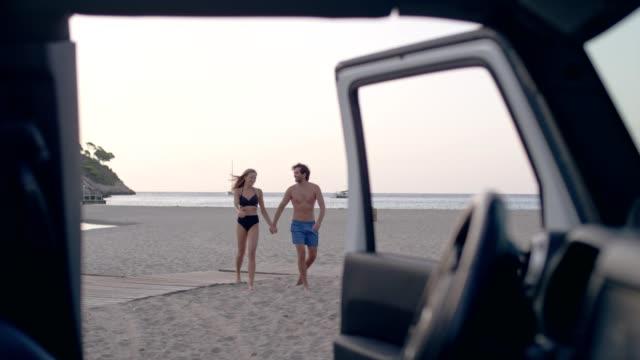 vidéos et rushes de jeune couple fuyant la voiture à la plage - homme faire coucou voiture