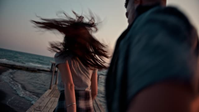 Young couple running holding hands on wooden jetty at sunset Young romantic hipster couple holding hands and running together on wooden jetty at sunset falling in love stock videos & royalty-free footage