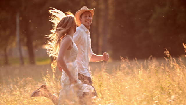SLO MO TS Young couple running in high grass video